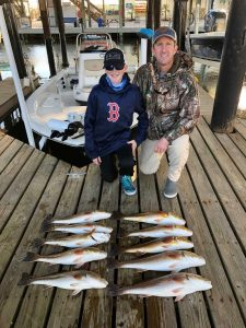 father and son with redfish that they caught on fishing trip