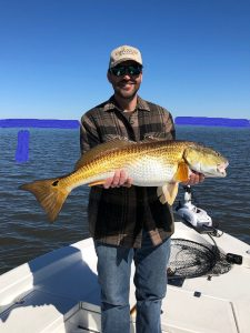 fisherman holding a large redfish on fishing trip with Victory Bay Charters