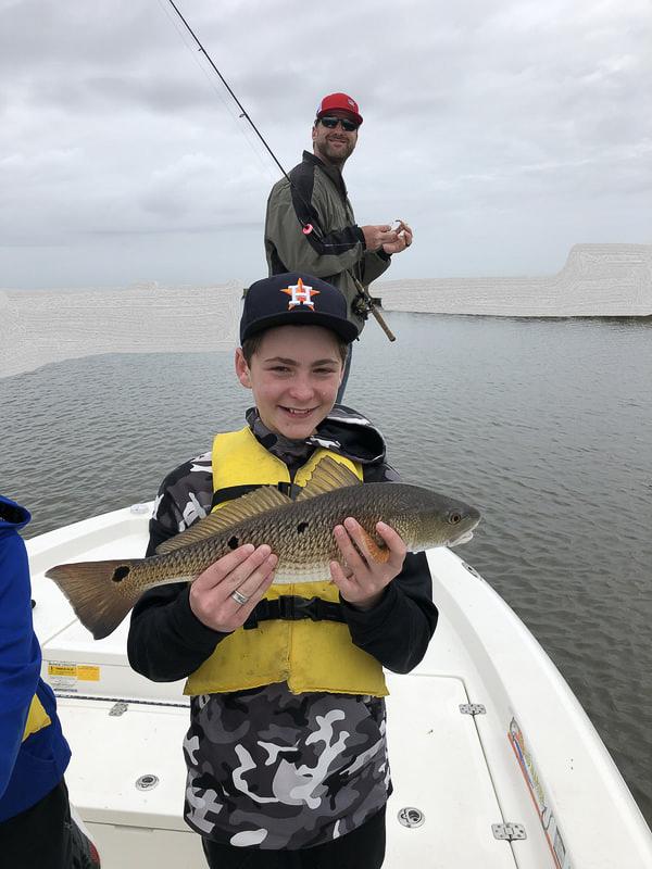 boy holding a medium size redfish on lake