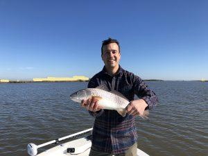 customer holding fish on boat