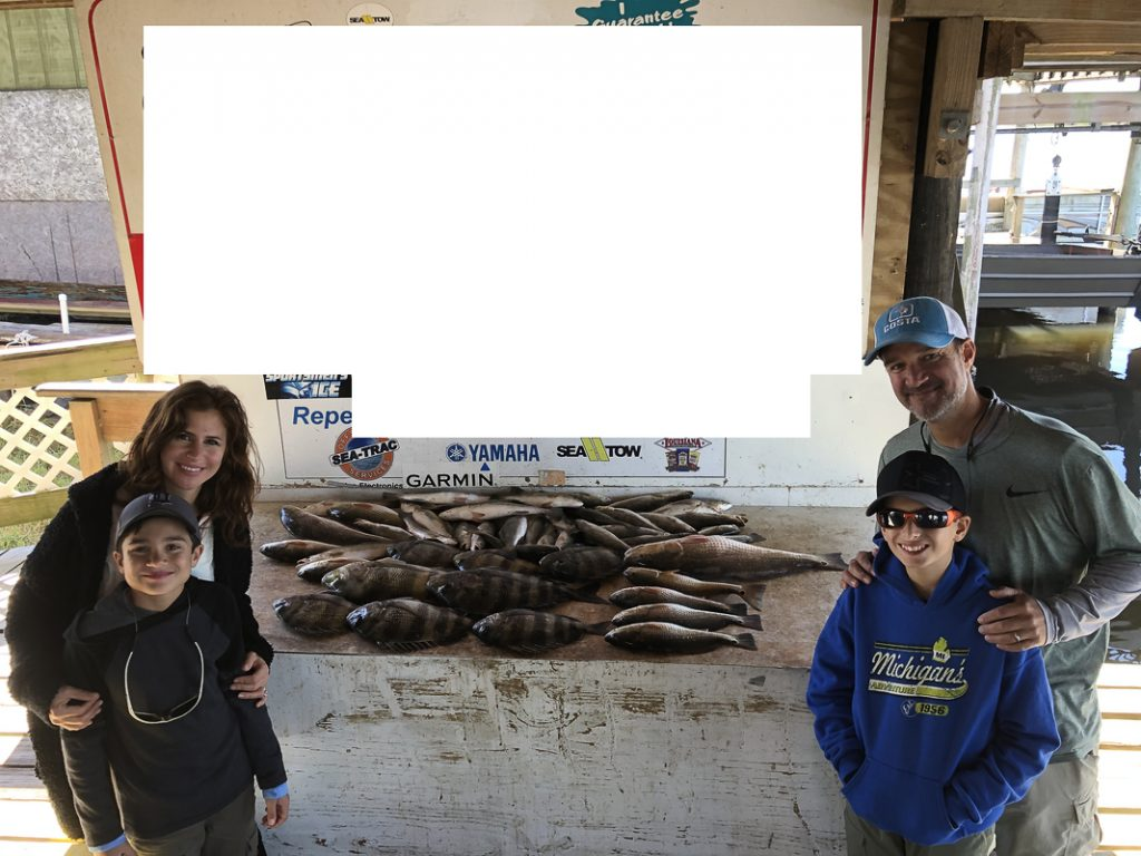 Family posing with fish that were caught