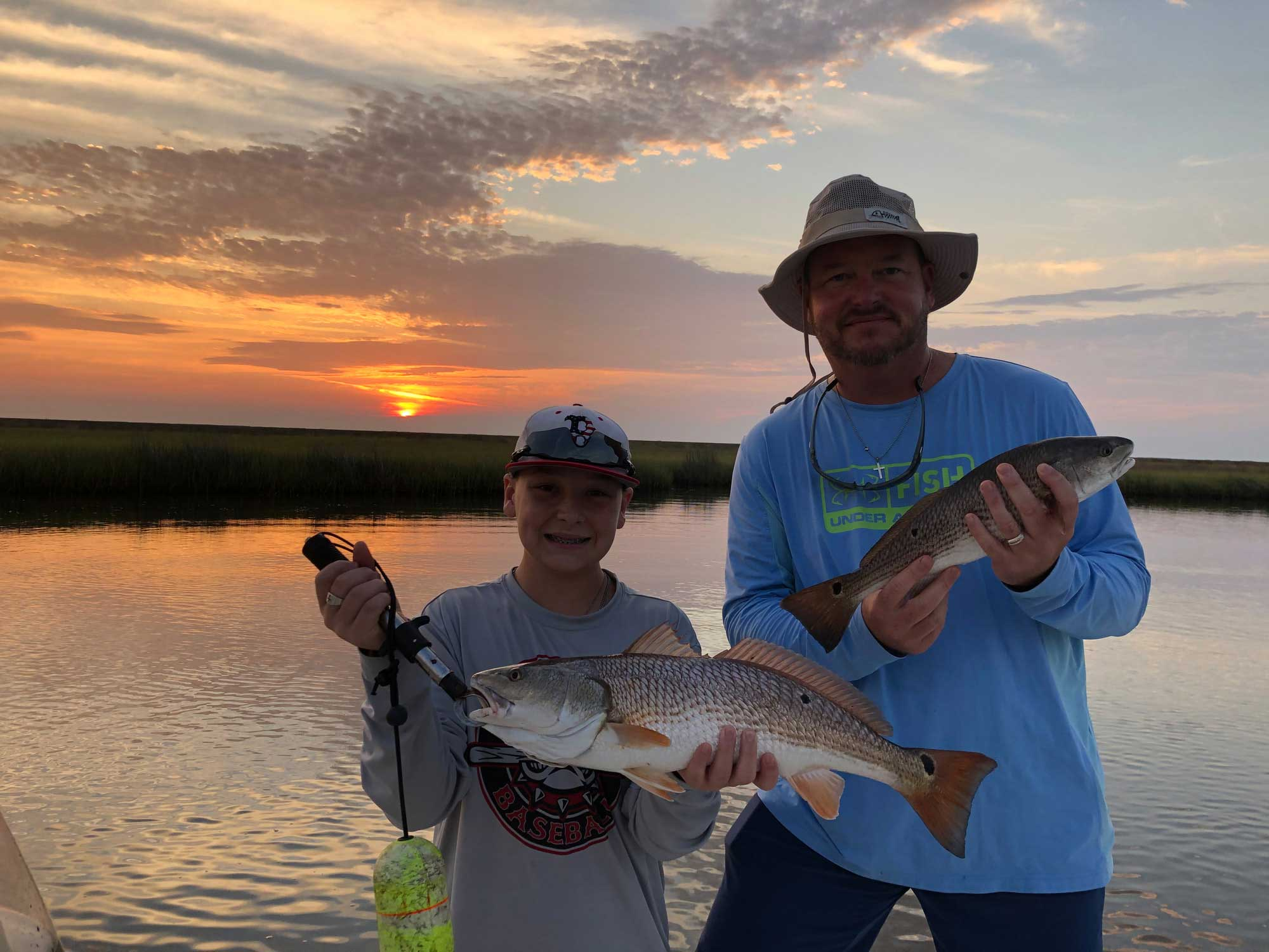 father and son holding two redfish during sunset in new orleans